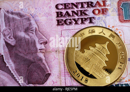 A close up image of a one ounce Chinese Panda gold coin with an Egyptian ten pound bank note - Stock Photo