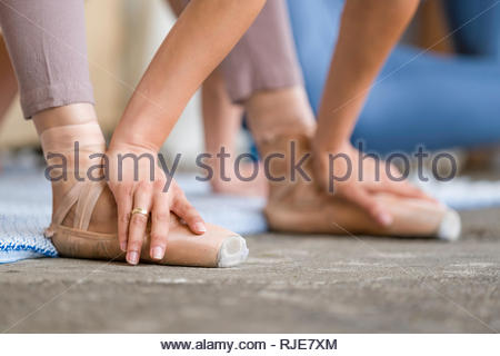 Female dancer stretching with hands on her ballet shoes during photography workshop on dance photography at the 2018 Fujifilm Festival, The Unlikely F - Stock Photo