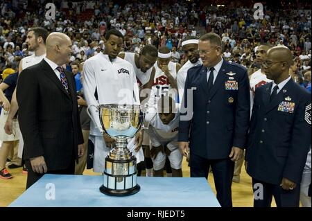 U.S. Air Force Maj. Gen. Bill Hyatt, U.S. Air Force Warfare Center commander, and Chief Master Sgt. Robert Ellis, U.S. Air Force Warfare Center command chief, stand with Andre Iguodala, USA Olympic Men's Basketball player, during the presentation of the player of the game award after an exhibition game against the Dominican Republic national team, July 12, 2012, at the Thomas and Mack Center, Las Vegas, Nev. Igoudala and the USA Olympic Basketball team are ready to continue  to the Olympic games in London, England. - Stock Photo