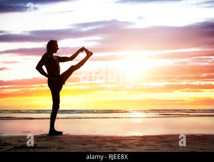 Fit Man in silhouette doing Yoga on the beach near the ocean at beautiful sunset in India - Stock Photo