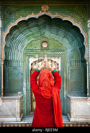 Indian Woman in red scarf with hands in prayer gesture at green gate door in City Palace of Jaipur, Rajasthan, India. Space for your text, can be used - Stock Photo