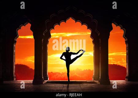 Man silhouette doing yoga advance balance asana in old temple at orange sunset sky background - Stock Photo