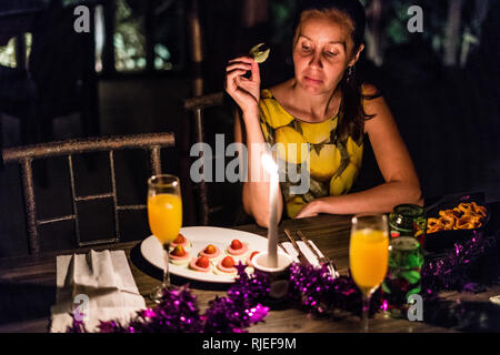 A nice portrait of a beautiful woman tasting her appetizer during a romantic dinner in a restaurant in a tropical rain forest of Costa Rica - Stock Photo