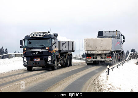 Salo, Finland - February 2, 2019: Two Volvo tipper trucks meet on a bridge during busy snow haul away from city to municipal snow dumping area. - Stock Photo