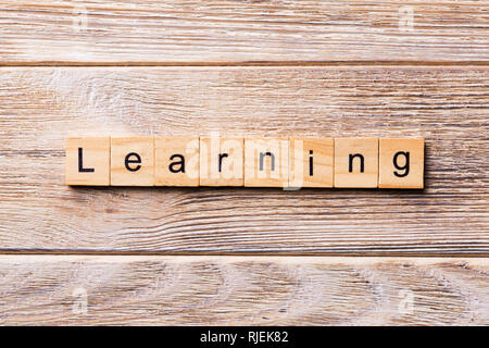 LEARNING word written on wood block. LEARNING text on wooden table for your desing, concept. - Stock Photo