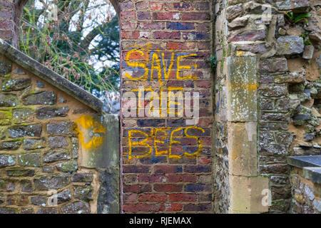 Save the bees graffiti and emblem scrawled on an old brick wall, uk - Stock Photo