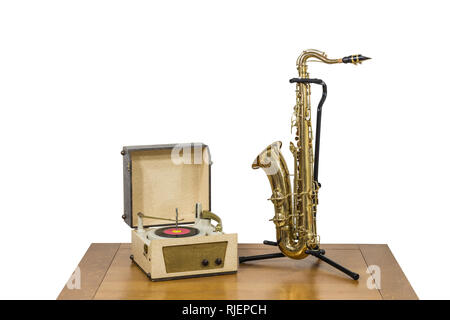 Old record player and saxophone on wood table isolated on white. - Stock Photo