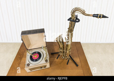 Vintage record player and saxophone on wood table. - Stock Photo