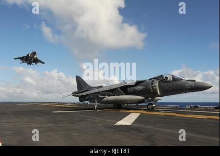 PACIFIC OCEAN (Oct. 19, 2016) AV-8B Harriers, assigned to Marine Medium Tiltrotor Squadron (VMM) 163 (Reinforced), land on the flight deck of the amphibious assault ship USS Makin Island (LHD 8). Makin Island, the flagship of the Makin Island Amphibious Ready Group, is deployed with the 11th Marine Expeditionary Unit in support of the Navy's maritime strategy in the U.S. 3rd Fleet area of responsibility. Stock Photo