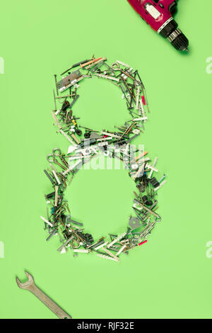 The conceptual composition from set of nails, screws and tools about Eight march womans day holiday on a green background. The number 8 in decor. Top view. The women in male occupations - Stock Photo