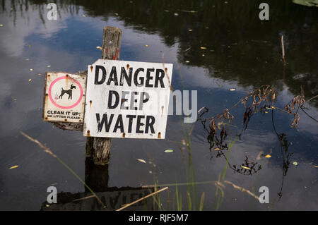 Danger Deep Water sign in a pond in a park in the UK. - Stock Photo