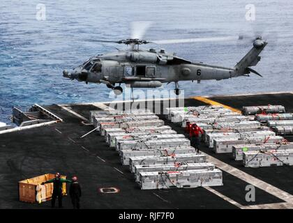 An HH-60H Sea Hawk helicopter assigned to the Indians of Helicopter Anti-submarine Squadron 6 airlifts ordnance off the flight deck of the aircraft carrier USS Nimitz during an ammunition offload with the Military Sealift Command dry cargo and ammunition ship USNS Wally Schirra. Nimitz is conducting blue water operations in the U.S. 3rd Fleet area of responsibility. - Stock Photo