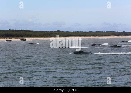 USTKA, Poland (June 17, 2015) Amphibious assault vehicles land at Ustka, Poland for the BALTOPS 2015 amphibious landing. U.S. Marines and service members from Finland, Sweden, the Netherlands, the United Kingdom, the U.S. Navy and the U.S. Army who comprise the BALTOPS Combined Landing Force and Combined Amphibious Task Force conducted the amphibious landing. BALTOPS, an annually recurring multinational exercise designed to enhance flexibility and interoperability, as well as demonstrate resolve of allied and partner forces to defend the Baltic region. - Stock Photo