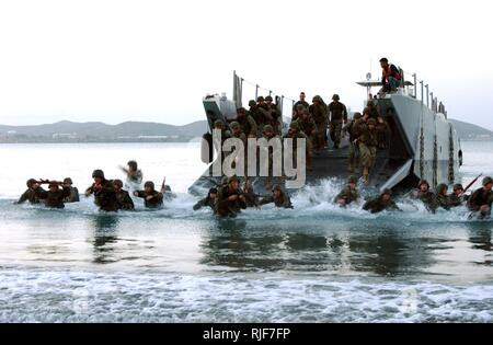 Guantanamo Bay, Cuba (June 23, 2004) Р Seventh Platoon, 1st Fleet Anti-terrorism Security Team (FAST) Marines and Sailors, exit a Landing Craft Utility (LCU) vehicle during a pre-dawn amphibious assault exercise in Cuba.  The exercise was modeled after the Nov. 20, 1943, Marine assault of the Tarawa Atolls during the World War II Pacific Campaign. U.S. Navy - Stock Photo