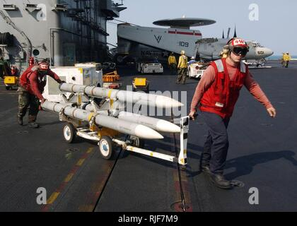 Arabian Gulf (Nov. 17, 2004) - Aviation Ordnancemen move a skid of AIM-120 Advanced Medium-Range, Air-to-Air Missiles (AMRAAM) across the flight deck of the conventionally powered aircraft carrier USS John F. Kennedy (CV 67). The AMRAAM is an all weather, beyond-visual-range weapon. The Kennedy Strike Group and aircraft from Carrier Air Wing Seventeen (CVW-17) are executing missions in support of ground troops in Fallujah Iraqi, under Operation Al Fajr (New Dawn). Units in the strike group are working closely with Multi-National Corps-Iraq and Iraqi forces to bring stability to the sovereign g - Stock Photo