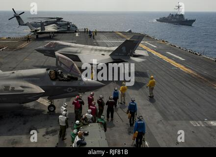 PHILIPPINE SEA (April 19, 2018) An F-35B Lightning II aircraft assigned to the 'Green Knights' of Marine Fighter Attack Squadron 121 (VMFA-121) maneuver on the flight deck of the amphibious assault ship USS Wasp (LHD 1) following a tactical recovery of aircraft and personnel. - Stock Photo