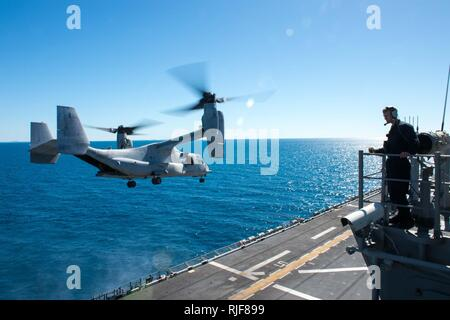 """CORAL SEA (July 20, 2017)  A Sailor observes an MV-22B Osprey assigned to the """"Dragons"""" of Marine Medium Tiltrotor Squadron (VMM) 265 (Reinforced) take off from the flight deck of the amphibious assault ship USS Bonhomme Richard (LHD 6) during Talisman Saber 17. Talisman Saber is a biennial U.S.-Australia bilateral exercise held off the coast of Australia meant to achieve interoperability and strengthen the U.S.-Australia alliance. - Stock Photo"""