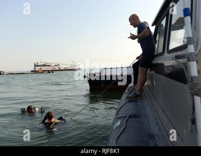 MINA SALMAN PIER, Bahrain (Jan. 24, 2013) Navy Diver 1st Class Ryan Marsh, assigned to Mobile Diving and Salvage Unit (MDSU) 2, Company 2-2, instructs divers surfacing from a routine anti-terrorism force protection dive. MDSU 2 is assigned to Commander, Task Group 56.1, promoting mine countermeasure, explosive ordnance disposal, salvage diving and force protection in the U.S. 5th Fleet area of responsibility. - Stock Photo