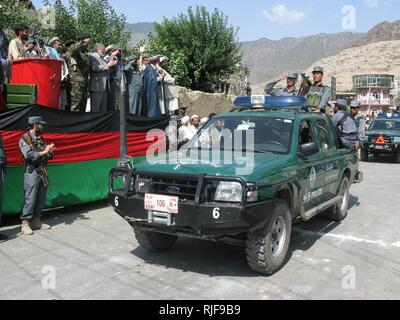 Konar's provincial governor, Gov. Sayed Wahidi (in the grey suit), applaudes the procession of Afghan national police and Afghan national army vehicles during the Independence Day Parade, downtown Asad Abad, Konar province, Afghanistan, Aug. 18, 2008. - Stock Photo