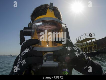 NAVAL SUPPORT ACTIVITY BAHRAIN (Jan. 06, 2016) Navy Diver 3rd Class Dakota Helm, assigned to Commander, Task Group (CTG) 56.1, conducts gear checks prior to conducting an anti-terrorism force protection dive. CTG 56.1 conducts mine countermeasures, explosive ordnance disposal, salvage-diving and force protection operations throughout the U.S. 5th Fleet area of operations. - Stock Photo