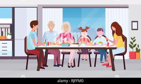 multi generation family sitting around table eating meal together happy grandparents parents and children modern kitchen interior flat horizontal - Stock Photo