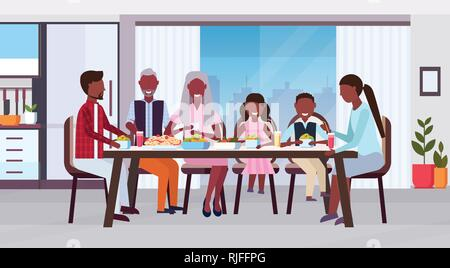 multi generation family sitting around table eating meal together happy african american grandparents parents and children modern kitchen interior - Stock Photo
