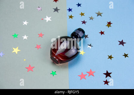 perfume bottle and glitter stars on green and blue background - Stock Photo