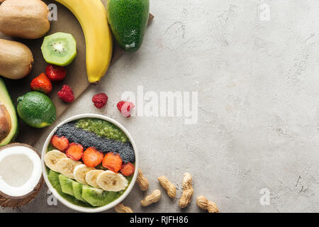 top view of smoothie bowl with fresh fruits and nuts on grey background - Stock Photo