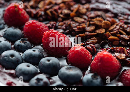 selective focus of blueberries, raspberries and homemade granola in smoothie bowl - Stock Photo