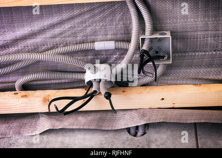 Electrical junction boxes with plastic corrugated pipes with electric cables in the process of installation on the ceiling with wooden planks. Close-u - Stock Photo