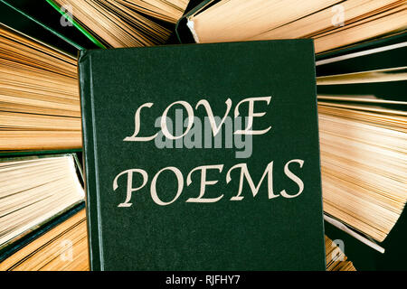 Top view of old hardcover books with book Love Poems on top. - Stock Photo