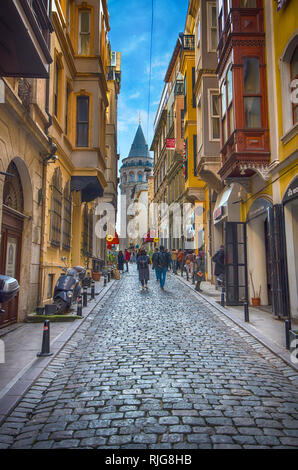 Galata Tower. This is a medieval stone tower one of the city's landmarks. The old narrow street in the historical district in Istanbul, Turkey - Stock Photo