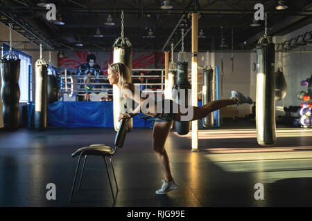 Young woman practicing yoga, doing Push ups or press ups exercise, phalankasana Plank pose, working out, wearing sportswear, grey pants, indoor, home