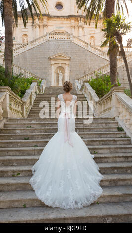 graceful bride climbs the stone stairs in a wedding dress - Stock Photo