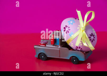 Pickup toy carrying one decorated easter egg on a pink background. - Stock Photo