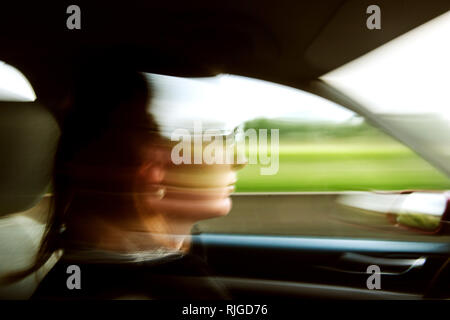 Abstract defocused silhouette of woman driving confident and fast in electric hybrid car with green fields in the background - Stock Photo