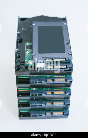 Elevated view of multiple HDD hard disk drives with modern fast SSD solid state drive placed above them - stack of it components to upgrade - Stock Photo