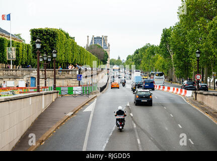 PARIS, FRANCE - MAY 21, 2016: Cars on the Quai des Tuileries street in central Paris with heavy traffic and Louvre museum in the background - Stock Photo