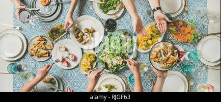 Flat-lay of hands holding mediterranean starters and drinks, wide composition - Stock Photo