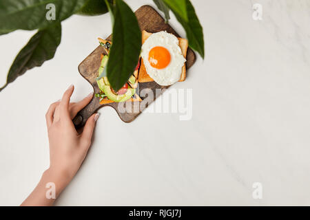 top view of womans hand holding wooden cutting board with toasts and scrambled egg under green plant on marble surface - Stock Photo