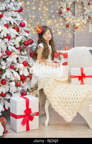 Christmas celebration. Cute little girl in a beautiful dress sitting near the Christmas tree. Christmas miracles. Luxurious Christmas decoration - Stock Photo