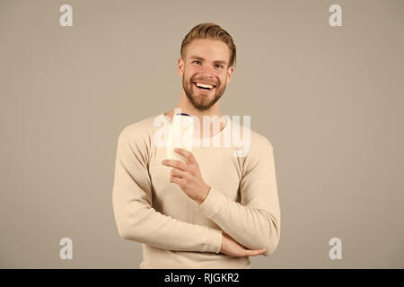 Hair care and beauty supplies concept. Man happy face holds shampoo bottle, grey background. Guy with bristle holds bottle shampoo, copy space. Man enjoy freshness after washing hair with shampoo. - Stock Photo