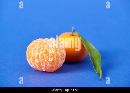 peeled organic tangerine near clementine with zest on blue background - Stock Photo