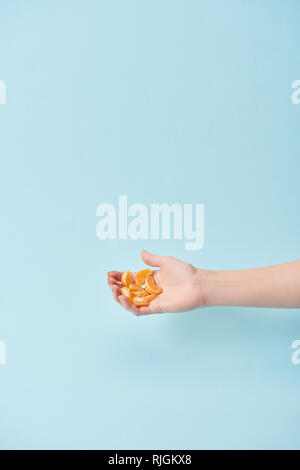 cropped view of woman holding slices of tasty peeled tangerine in hand isolated on blue - Stock Photo