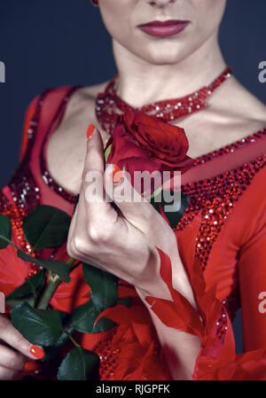 Rose flower in female hand on red dress. Love, desire, romance. Floristry, decor, design, floral shop. Womens day, 8 march spring Birthday anniversary holidays celebration - Stock Photo