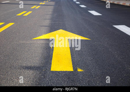 Arrow mark on asphalt , showing the highway traffic direction. - Stock Photo