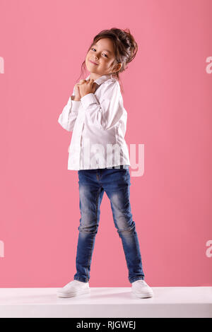 Full length portrait of adorable smiling little girl in white shirt with hairstyle looking to camera on pink background. - Stock Photo