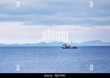 Blue trawler fishing boat sailing over the calm sea in a cloudy winter day in Gumusluk, Bodrum, Turkey. - Stock Photo