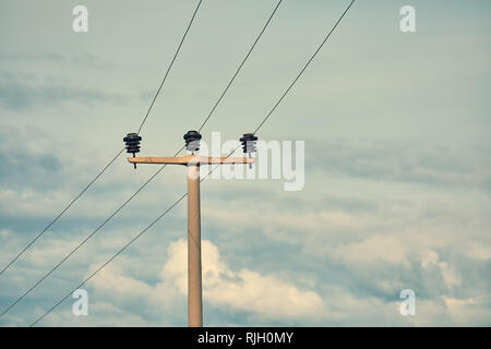 Minimalist view of a concrete high voltage power electric pole, power lines and fuses against a cloudy blue sky background. - Stock Photo