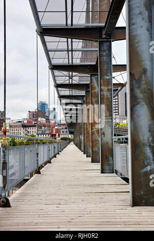 Old bridge made of wooden plank floorboard and metal steel girder in the city - Stock Photo